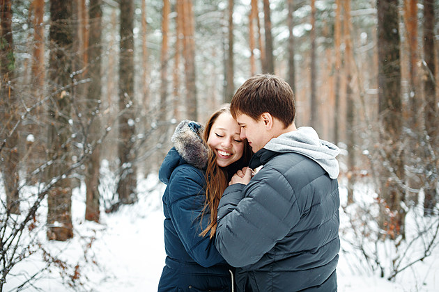 Couple in love having fun in winter forest